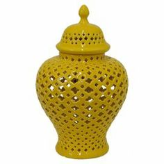 """Brimming with eye-catching style, this curving jar showcases an openwork quatrefoil design and finial lid.     Product: Lidded jarConstruction Material: Ceramic and porcelainColor: Yellow Features: Open work design  Dimensions: 11"""" H x 7"""" Diameter"""