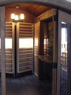 Traditional wine cellar by Red Ridge Wine Cellars with section hidden by opening shelves.