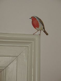 Bird on a doorframe - I love this idea for a little unexpected burst of color and happy in my home :) Specifically for bathroom.