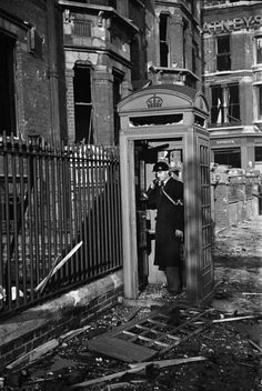 An air-raid Warden phoning from a shattered telephone box, London, By George Rodger, 1940