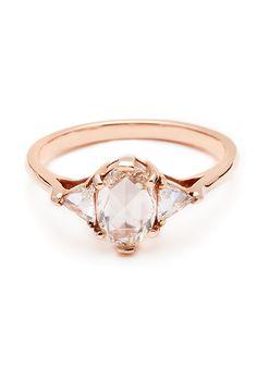 "Brides.com: . ""Oval Bea"" rose-cut diamond center with white diamond trillion side stones set in 14K rose gold, $5,000, Anna Sheffield"