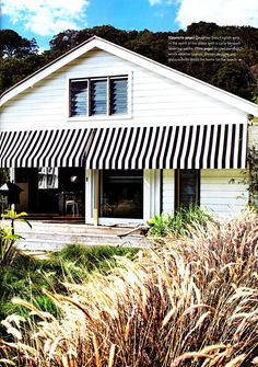 black and white striped awnings on white weatherboard house. http://www.modularhomepartsandaccessories.com/awningideas.php has some information on awnings that are available in the marketplace.