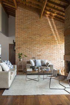 Casa de campo aconchegante tem parede de tijolos e soluções sustentáveis