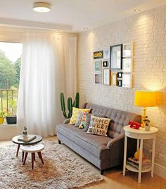 Sofá cinza, abajur amarelo, textura na parede, quadros.