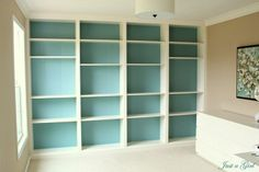 DIY Bookcase wall using prefab Ikea bookcases, wood trim, crown molding, caulk, and some paint. Office/nursery?