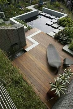 Clever modern garden using variegated agave to match with the dark tones of the wooden furniture throughout.