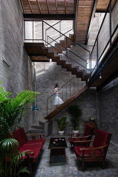 Zen House. H.A. Vietnam. © Quang Dam Palier. Escalier magistral. Lattes de bois. Structure métal. Naturel. Briques. Béton. Lumière tamisée. Zen. Puit de lumière. Unrefined brick. Wood. Unpainted cemboard. Ferrous iron. Natural lighting.