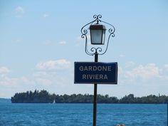 Een naambord van Gardone Riviera met het Gardameer en Isola del Garda op de achtergrond