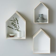 Quirky yet stylish set of box shelves in the shape of a house.   - Light wood with white interiors and hooks on the back to mount on the wall.  - Danish design.