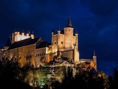The Alcázar of Segovia is a castle, located in the old city of Segovia, Spain. Rising out on a rocky crag above the confluence of two rivers near the Guadarrama mountains, it is one of the most distinctive castle-palaces in Spain by virtue of its shape – like the bow of a ship. The Alcázar was originally built as a fortress but has served as a royal palace, a state prison, a Royal Artillery College and a military academy since then. It is currently used as a museum and a military archives…