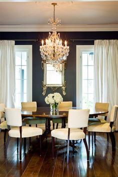 bold and beautiful dining room--charcoal walls, sparkling gold and crystal, modern round table and chairs, wide plank wood floor...