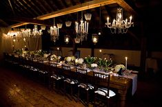 Mismatched chandeliers hung directly over table. No other twinkly lights or drapes. Low flowers on table runner.