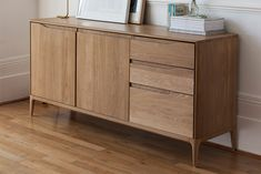 Oak sideboard available in various sizes and configurations. Solid Oak sideboard with soft curves. Two separate cupboard sections and three drawers with soft-close mechanisms. Door and drawer handles with wave-shaped cut-out recesses.