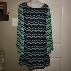 Chevron Dress A gorgeous size medium dress from the brand xhiliration bought from Target it's got long sleeves that flow out and are pleated the entire dress is 100% polyester so it feels silky smooth to the touch!!! The sleeves measure 25inches long and from the shoulders to the hemline it measures 36inches in length the dress is navy blue and teal in color and has a cute chevon pattern it's in excellent condition from a smoke free house Xhilaration Dresses