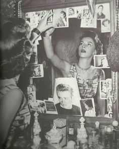 Natalie Wood puts up pictures of James Dean in her dressing room after his death