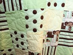 Baby Quilt: Yellow, Green, and Brown. Monkey themed with banana motif on solid blocks, plus over-quilting of patterned blocks. Handstitched.