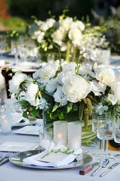 White peonies are paired with roses and calla lilies for a more modern wedding centerpiece.