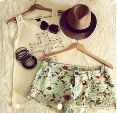 White shirt mint green flowery shorts black bracelets glasses and brown hat
