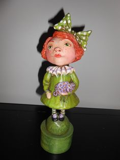 ST. Patty's Girl, 2013  a green eyed girl . A sculpted collar and a bunch of purple flowers.A bow in her hair. A simple lassie for display. Antiqued and mounted on a cardboard base. Original by Debra Schoch   Paper Clay Material.