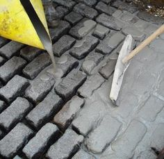 Applying Flowpoint to traditional natural stone road cobbles.  Pour in, squeegee over and rinse-off with water.  Available from Arcon Supplies.