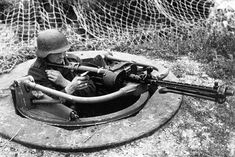"""A German gunner in a concrete """"ringstand"""" foxhole with an MG34 machine gun somewhere in the Netherlands. The ringstand Type 58c, also known as a """"Tobruk"""", was a German concrete pillbox for a machine gun built in the fall and winter of 1944 as part of the Maas-Ruhr defense line."""
