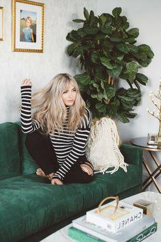 Lange blonde Haare mit Pony, gestreifte Bluse und schwarze Hose, leichtes Make up