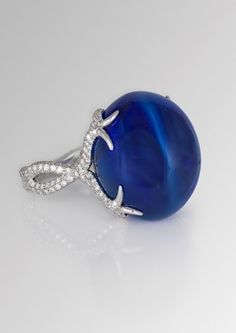 David Morris ring featuring a central 64.55ct blue Burmese double cabochon sapphire with a twisting diamond band