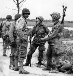 """Two paratroopers, probably with the 507th PIR, 82nd Airborne Division, meet with GIs of the 90th Infantry Division """"Tough """"Hombres"""", preparing to relieve the """"All American"""" troopers. Cretteville-Baupte Sector, Utah Beach, Normandy. 20 June 1944."""