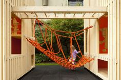 Kids' recreation installation with wooden structure, monkey bars, and rope bridge.