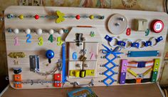 A busy board for children 1 - 3 years. Size: 40 x 80 cm (16 x 32 inches). Weight about 4 kg. All items are securely fastened . For your childs safety must be adult supervision. This toy helps develop self-help skills. Here you will find the elements that attract the attention of the child: a house with different fasteners and pictures cut out from fabric, light switch, red lamp (batteries not included), wheel, rotating with knob in both directions and other interesting things. A design idea…