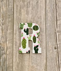 big little reveal themes This succulent letter is my best seller! The pearly white background paired with the 5 different shades of green and the small designs. To top it off, r Cactus Wall Art, Cactus Decor, Cactus Print, Sorority Decorations, Sorority Crafts, Paper Mache Letters, Hanging Letters, Painted Letters, Wooden Letters