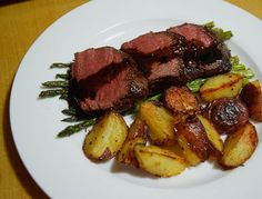 A beautifully plated plate of asparagus topped with venison loin medallion and a balsamic pan sauce