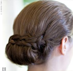 "Alyson asked her hairstylist to create an elegant, interesting, and organic look for her wedding day. She ended up with a low updo with a braid on one side and knots on the other, accented with a fresh, white phalaenopsis orchid. ""I'm so happy with the wa..."