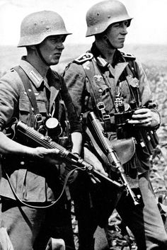 A private and a sergeant major just decorated with the Iron Cross 2nd Class for their valor during the Battle of Kerch in the Crimea pose for the photographer carrying their MP-38 submachine guns. (Summer 1942)