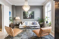 Lys stue med store vindusflater, samt stukkatur og rosetter i himling.