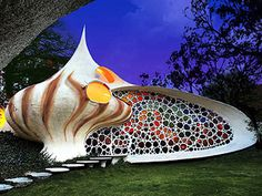 The Nautilus - Mexico City, Mexico   This seashell-shaped home was completed in 2006. The stone steps running along the shrubs lead to the front door, which blends into the mosaic façade.