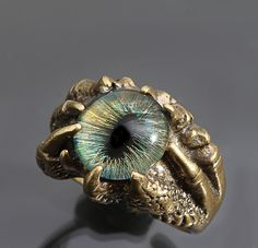 A golden brass claw ring accented with a hand painted dragon eye.   No two eyes are ever the same as they are meticulously hand painted in a variety of colors with a black pupils and tiny detailed black veining.  The dragon claw ring has been given a patina, hand buffed back to show golden highlights and sealed inside and out.  For those who love DRAGONS!  dragon / dragon claw / dragon eye / evil eye / ring  37.50