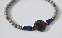 This Designs by s.e.K bracelet features a round labradorite stone, surrounded by brushed brass, triangular lapis lazuli and round black spotted feldspar beads, closed with an antique copper-plated brass button clasp.