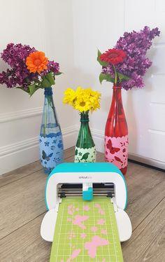 Une belle idée d'upcycling pour nos tables ! Prenez des bouteilles en plastique de différentes couleurs, découpez avec votre Cricut de jolis motifs récupérés sur le Design Space et une fois les motifs collés à l'aide de la bande de transfert Tape, vous obtinedrez de jolies bouteilles- Autre usage, @mamanswinneuses en a fait des vases. Cricut, Cute Diys, Aide, Vases, Easy Diy, Group, Board, Fun, Design