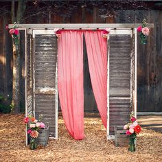 rustic wedding altar made of weathered shutters and gauzy pink fabric, complete with colorful flowers