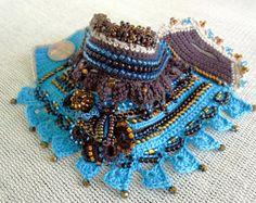 nique abalorios ganchillo pulsera brazalete en colores blancos, luz azules, turquesa azules y melocotónes.  Esta pulsera de crochet de hilo de algodón 100%, está decorado con rocallas de cristal, granos del preciosa y chips de turquesa. Тhe son las variantes de colores azul, blanco y melocotónes. La pulsera está hecha con los granos de alta calidad. La pulsera están decoradas con mini flores de ganchillo con cuentas.  Hice este brazalete utilizando una técnica de Crochet de forma libre y…