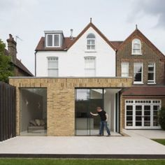 This London house extension by Tigg Coll Architects features sliding glass doors that retract into the brick walls to open the space up to the garden Architecture Design, Facade Design, Exterior Design, House Design, Brick Extension, Rendered Houses, Terrasse Design, Architects London, Brick Facade