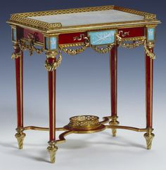 This Fabergé miniature Louis XVI style table, 1903, one of two acquired by Queen Mary, shows Michael Perchin's clever use of gold and enamel. Red guilloché enamel replicates the grain of wood veneer and blue and white enamel imitates inset porcelain plaques. On the lid, mother-of-pearl replicates the writing surface and is engraved at the four corners with the Romanov double-headed eagle.