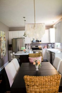 KITCHEN/DINING AREA: Dark Wood Table with White Upholstered Chairs, White Kitchen, and Chandelier