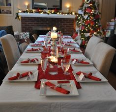 Beautiful Christmas Party Table Setting On Adorable Rectangular Dining Table With Soft White Table Cloth And Pretty Christmas Tree Near Comfort Fireplace Also Magnificent White Candle On Glass Plus Awesome Cutlery On Table For Christmas Day