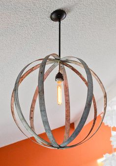 Wine barrel rings were used to make a chandelier to hang on a vaulted ceiling. The antique sphere was purchased at the Alameda Antique Fair and we fitted lamp hardware to complete the piece. A filament bulb was added to continue the antique feel.