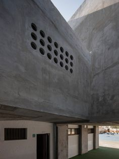 Tiny porthole windows cast polka-dot patterns of light across the exposed concrete interior of this school