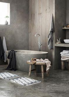 Minimalist bathroom with a concrete bathtub, and concrete floors