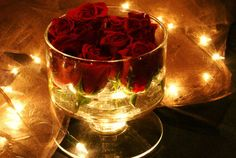 roses in a glass bowl with fairy lights