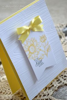 luv the look of white embossed with wood grain ... clean and simple style ... yellow and white ... wide fish tail banner as focal pane ... sunflower line drawing stamped in yellow ... perfect bow ... great card!!
